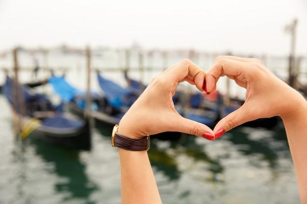 A forma di cuore realizzato con le mani con splendida vista sulle gondole Foto Premium