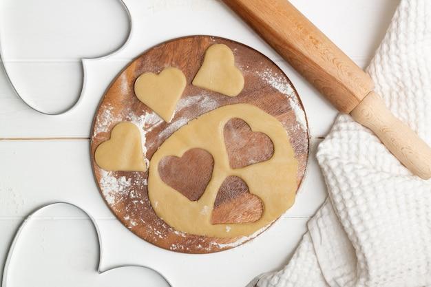 Uno stampo a forma di cuore e biscotti tagliati con pasta accanto a un asciugamano e cucchiai di legno e mattarello, distesi. Foto Premium