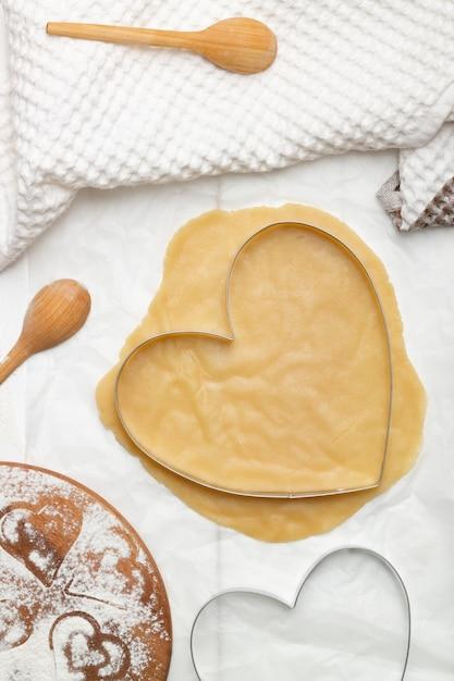 Uno stampo da taglio a forma di cuore su pasta arrotolata accanto a un asciugamano e cucchiai di legno. lay piatto, verticale Foto Premium