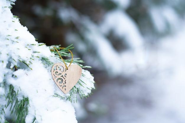 Cuore sulla neve sui rami di abete in inverno, concetto di sfondo vacanza di san valentino. Foto Premium