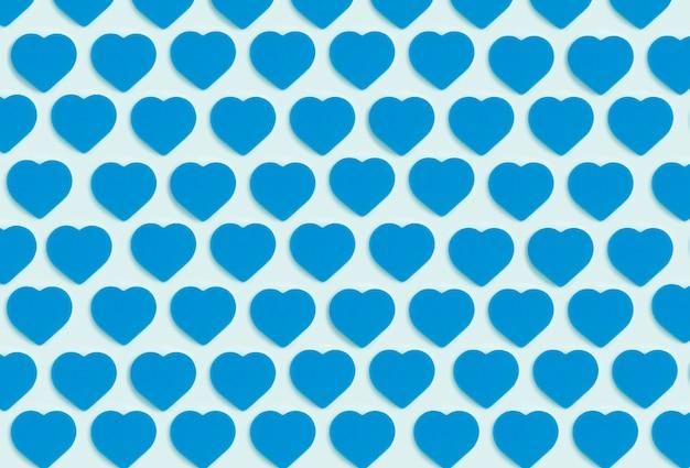 Sfondo di cuori. ornamento colorato da ritagliare cuori blu su sfondo blu. amore, romanticismo, carta da parati, concetto minimo di cartolina Foto Premium