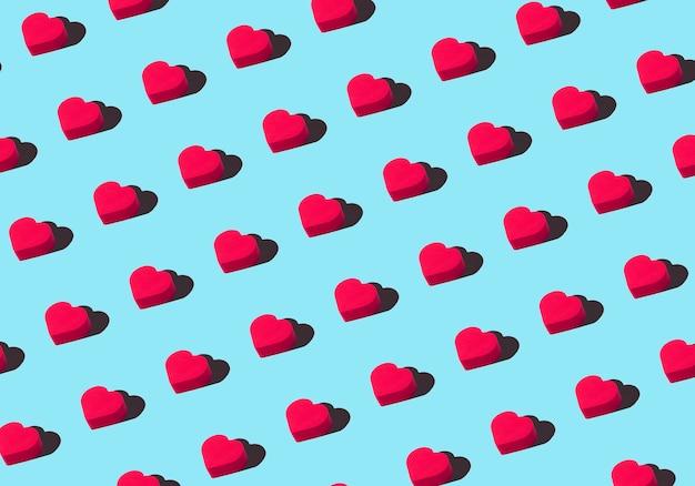 Sfondo di cuori. ornamento colorato da cuori rossi ritagliati su sfondo blu. amore, romanticismo, carta da parati, concetto minimo di cartolina Foto Premium