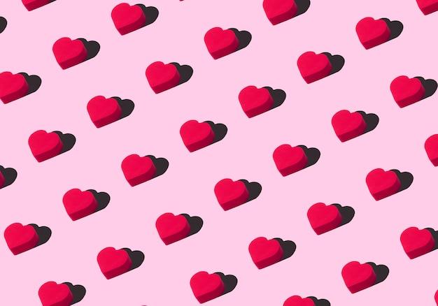 Sfondo di cuori. ornamento colorato da ritagliare cuori rossi su sfondo rosa. amore, romanticismo, carta da parati, concetto minimo di cartolina Foto Premium