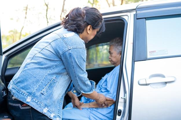 Aiuta e supporta il paziente asiatico anziano o anziano della donna anziana ad arrivare alla sua auto Foto Premium