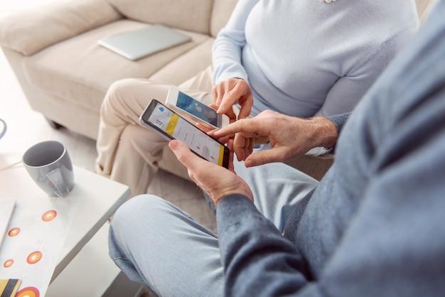 Tecnologie utili. il primo piano di una coppia di anziani seduta in soggiorno e che controlla le previsioni del tempo sui loro telefoni, confrontandole Foto Premium