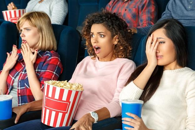 Ecco che arriva la parte spaventosa. un ritratto di tre belle amiche che gridano e che sembrano spaventate mentre guardano un film insieme nel cinema Foto Premium