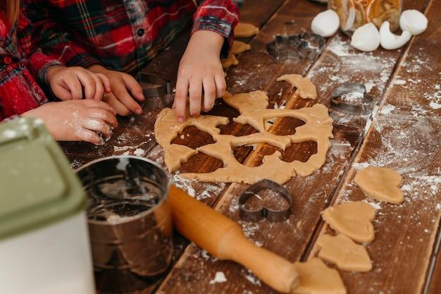 Bambini ad alto angolo che producono biscotti insieme a casa Foto Premium