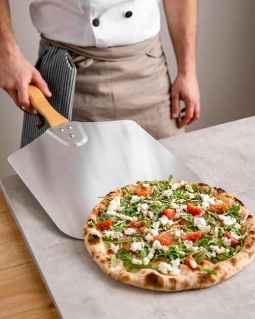 Uomo ad alto angolo afferrando la pizza con lo strumento di buccia Foto Premium