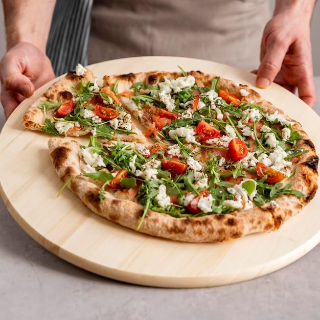 Persona di alto angolo che afferra la fetta di pizza fresca Foto Premium
