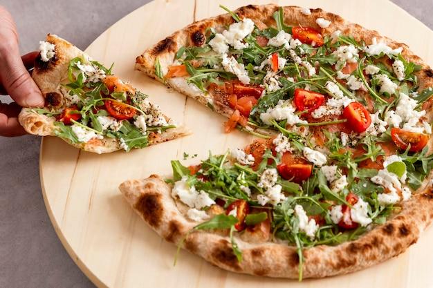 Persona ad alto angolo afferrando la fetta di pizza Foto Premium
