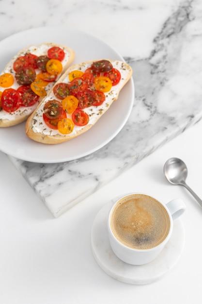 Panini ad angolo alto con crema di formaggio e pomodori sulla piastra con caffè Foto Premium