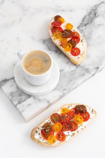 Panini ad angolo alto con crema di formaggio e pomodori con tazza di caffè Foto Premium