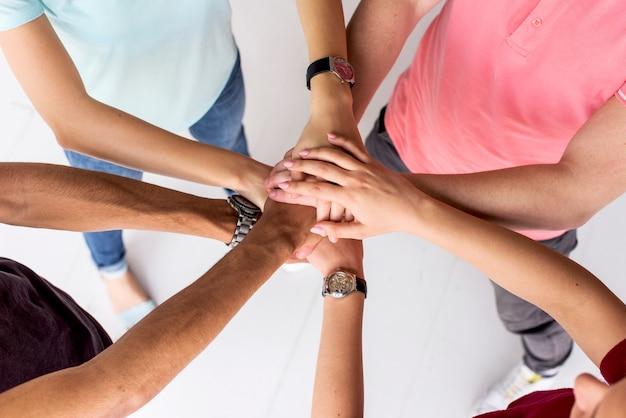 Punto di vista dell'angolo alto degli amici che impilano insieme le loro mani Foto Premium