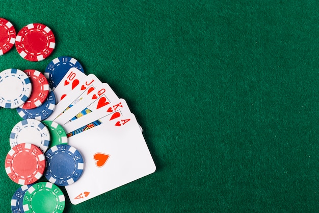 Vista dell'angolo alto dei club e delle patatine di vampata reale sul tavolo verde del poker Foto Premium