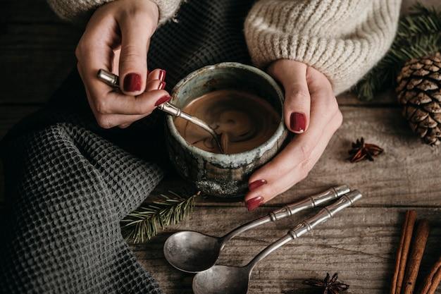 Tazza della holding della donna di alto angolo con cioccolata calda Foto Premium
