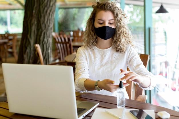 Donna ad alto angolo utilizzando disinfettante per le mani Foto Premium