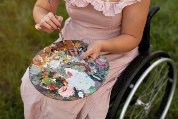 Alto angolo di donna in sedia a rotelle con tavolozza di vernice Foto Premium