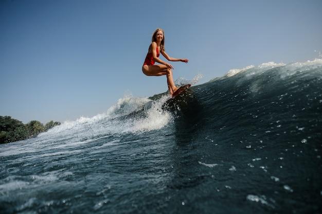 Onda blu alta in primo piano e bella donna bionda, navigare a bordo Foto Premium