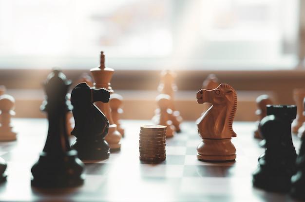 Alta luce chiave di due cavalli di scacchi uno di fronte all'altro con stack nuove monete da una sterlina britannica nel mezzo del gioco da tavolo. Foto Premium