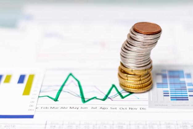 Mucchio di alta vista di monete su diagrammi statistici Foto Premium