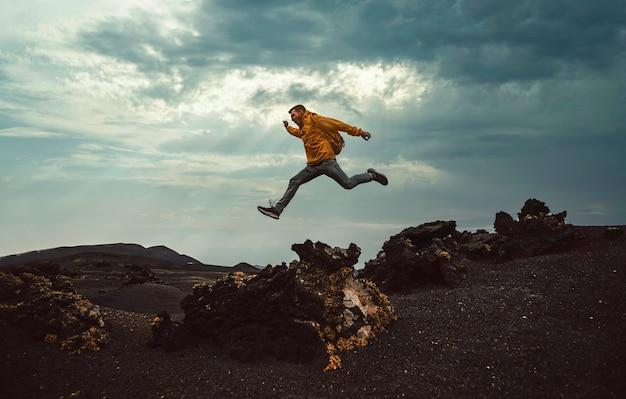 Uomo della viandante che salta sopra la montagna. libertà, rischio, successo e sfida. concentrati sull'uomo Foto Premium