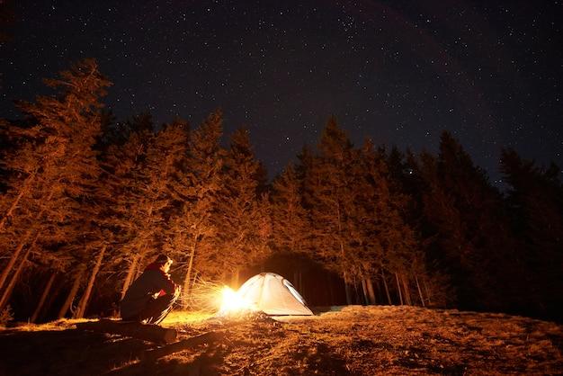 Escursionista vicino al fuoco e tenda turistica di notte Foto Premium