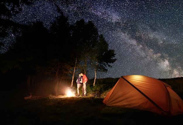 Escursionisti vicino al fuoco e alla tenda durante il campeggio notturno Foto Premium
