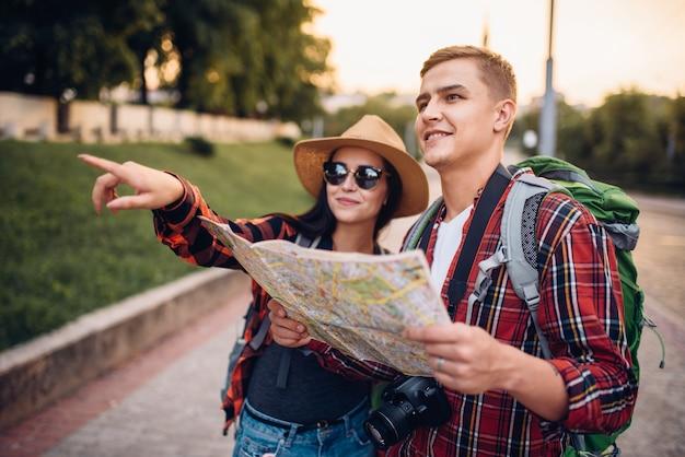 Escursionisti con zaini alla ricerca delle attrazioni della città sulla mappa, escursione in località turistica. escursioni estive. escursione all'avventura di un giovane uomo e una donna Foto Premium