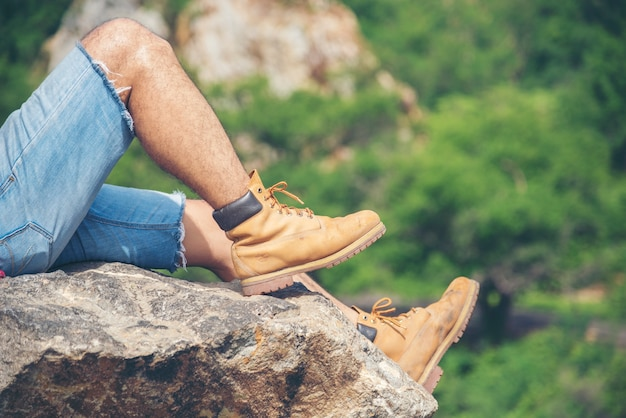Escursionismo a piedi sulla montagna con esploratore di scarponi da trekking marroni su rock mountain view. concetto di stile di vita di libertà di viaggio dell'uomo di avventura. Foto Premium