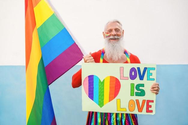 Uomo anziano hipster al gay pride che tiene bandiera arcobaleno e banner lgbt - focus sul viso Foto Premium