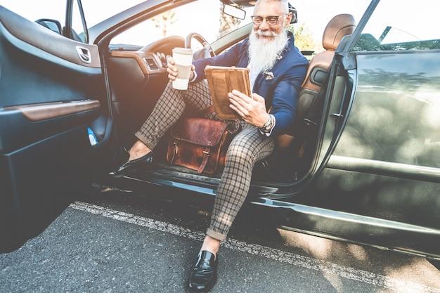 Uomo alla moda hipster utilizzando la tavoletta seduto all'interno di un'auto elettrica convertibile - imprenditore senior divertendosi con le tendenze della tecnologia - tecnologia, sistemi ecologici e concetto di moda - focus on face Foto Premium