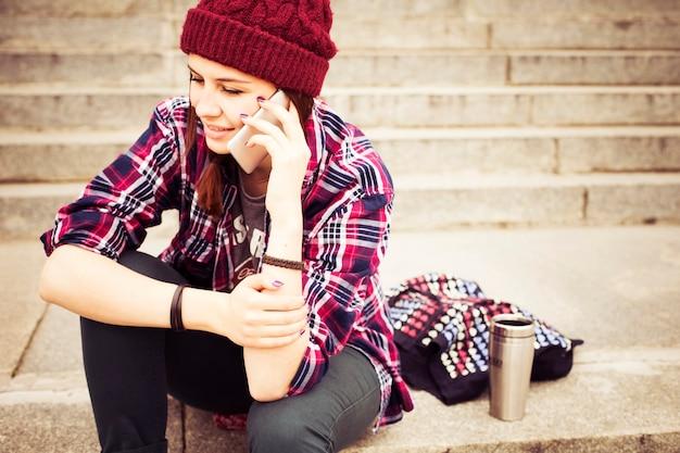 Donna hipster in abito casual seduto sui gradini in città, facendo telefonata Foto Premium