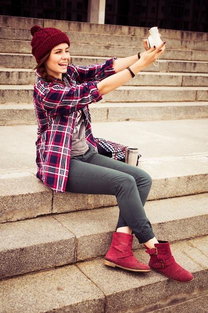 Donna hipster in abito casual seduto sui gradini in città, facendo selfie sulla fotocamera istantanea Foto Premium