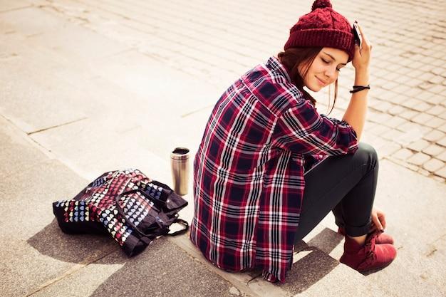 Donna hipster in abito casual seduto sui gradini in città con un telefono in mano Foto Premium