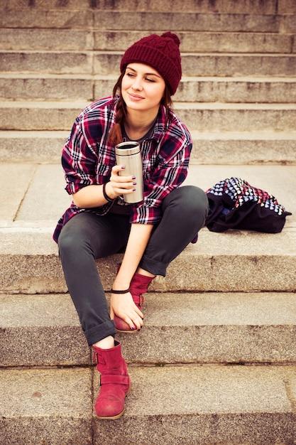 Donna hipster in abito casual seduto sui gradini in città Foto Premium
