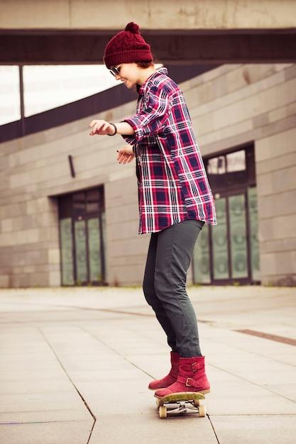 Donna hipster in abito casual skateboard in città Foto Premium