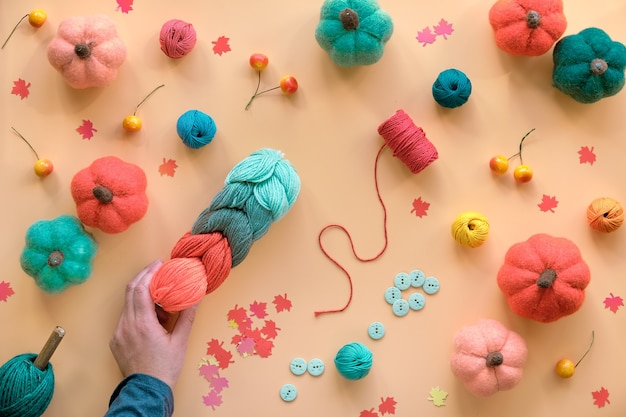 Hobby craft lay flat. sfondo stagionale autunnale con zucche di lana feltro fai-da-te, fascio di lana, bottoni e bacche. Foto Premium