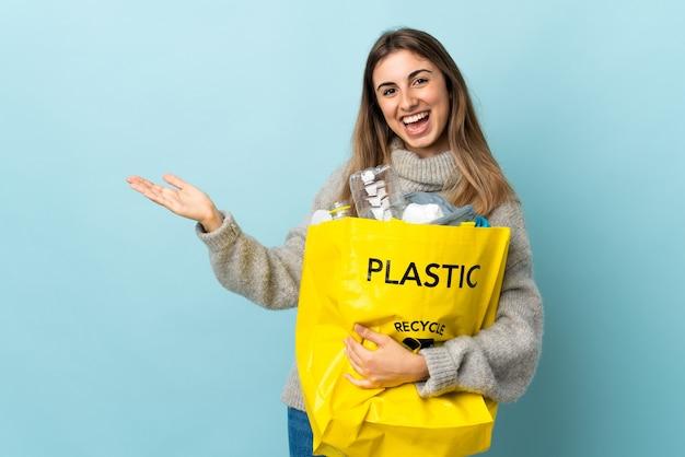 Tenendo una borsa piena di bottiglie di plastica da riciclare sopra le mani blu isolate che si estendono di lato per invitare a venire Foto Premium