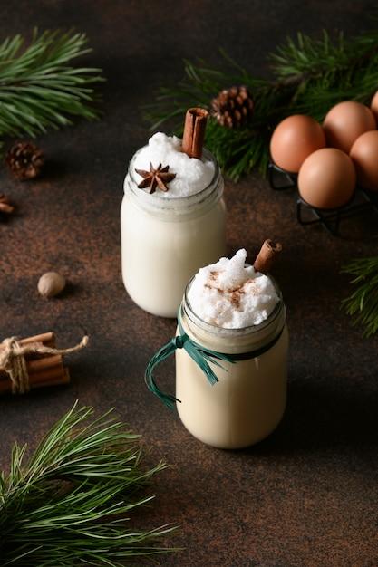 Vacanza zabaione bevanda di natale in barattolo di vetro con cannella e noce moscata su sfondo marrone Foto Premium