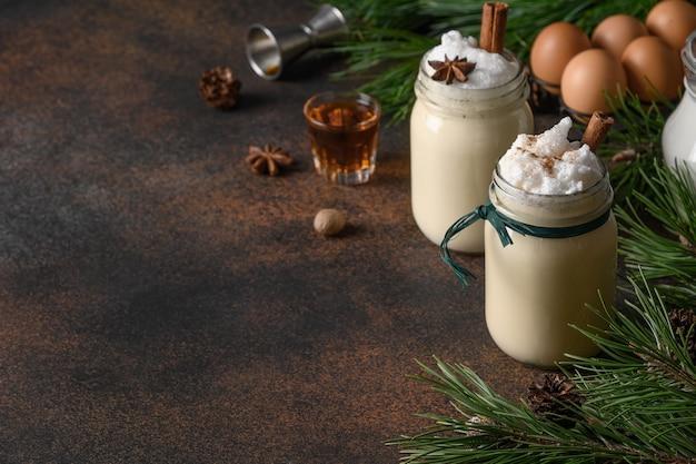 Zabaione di natale di festa in barattolo di vetro con spezie e alcool su sfondo scuro. avvicinamento. Foto Premium