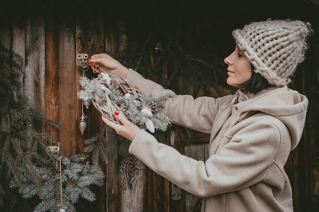 La donna delle decorazioni natalizie crea un'atmosfera natalizia all'aria aperta, rustica e minimalista, moderna con materiali ecologici naturali in stile scandinavo. idee che decorano il nuovo anno con le tue mani fatte a mano. Foto Premium