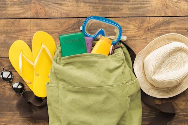 Sfondo di estate viaggio vacanza zaino viaggiatore con passaporti e oggetti di vacanza sulla vista del piano del tavolo in legno Foto Premium