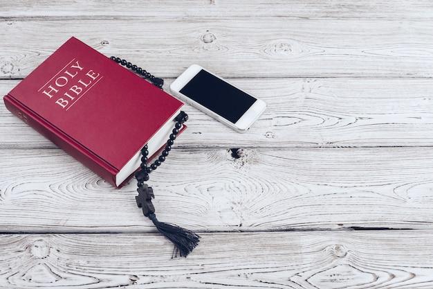 Sacra bibbia e smartphone con una tazza di caffè nero su superficie di legno. Foto Premium