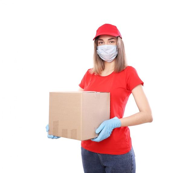 Consegna a domicilio, ordine online. corriere femminile in una maschera medica e guanti di gomma con una scatola, con un pacco in mano. consegna del cibo durante la pandemia di quarantena del coronavirus Foto Premium