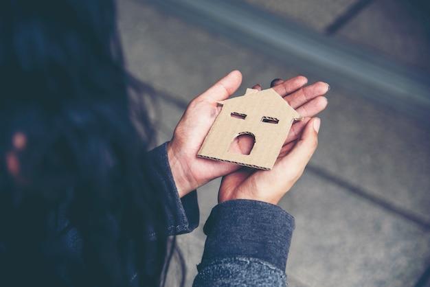 Casa nelle mani di senzatetto povertà mendicante uomo sogno con dolce casa cerca di chiedere lavoro soldi e sperando aiuto in impotente città sporca seduta per strada Foto Premium
