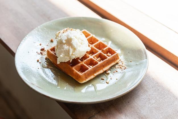Waffle classico fatto in casa topping con una pallina di gelato alla vaniglia. topping con mandorle tritate e sciroppo d'acero. servito in un piatto di ceramica. Foto Premium
