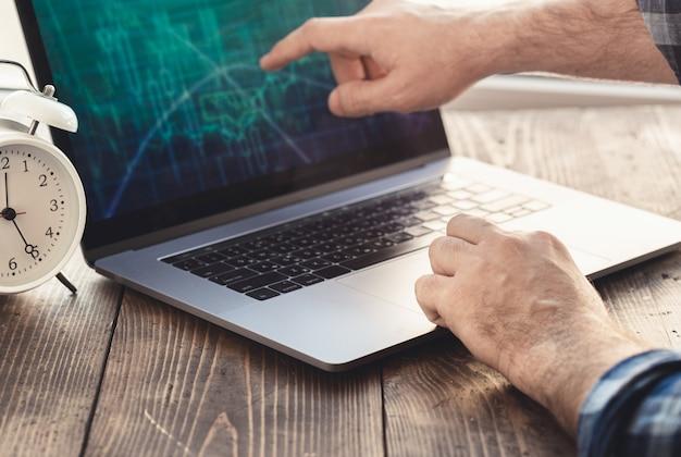 Posto di lavoro a casa. l'uomo analizza e controlla il grafico sul computer portatile Foto Premium