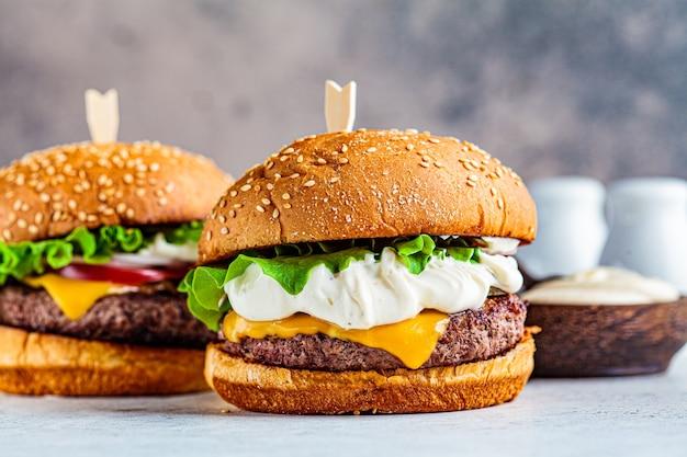 Hamburger di manzo fatti in casa con formaggio, maionese, sottaceti e verdure, sfondo grigio. Foto Premium