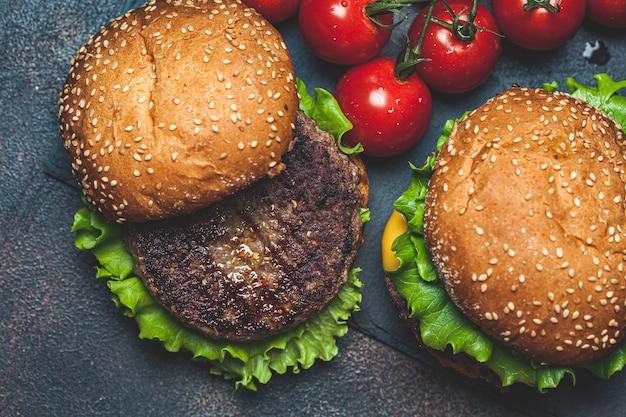 Hamburger fatti in casa con cotoletta di manzo, formaggio e verdure, uno sfondo scuro, vista dall'alto. Foto Premium