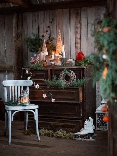 Decorazioni natalizie fatte in casa su una terrazza rustica con cassettiera vintage e candelabri fatti a mano per festeggiare il natale Foto Premium